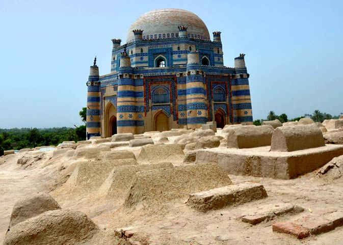 The tomb of Bibi Jiwandi set against a mass of small, cemented graves. The area in itself is the patch of desert preserved in the area and is surrounded by lush green vegetation.