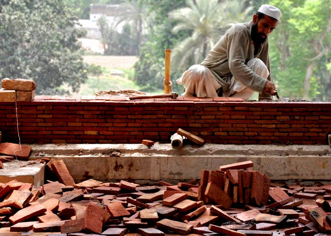 A bricklayer works on constructing a new wall around the main Uch Sharif enclosure.