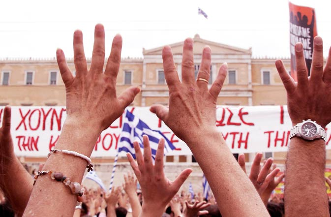 Demonstrators raise their hands in the traditional Greek insult gesture in front of the Greek Parliament. - Reuters Photo