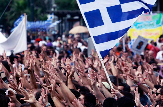 Protesters gesture and wave Greek flags in front of the Parliament. - AP Photo