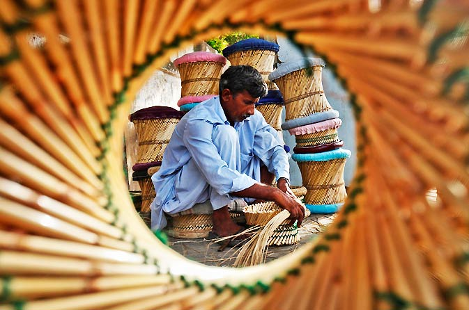 Iqbal, 42, is framed through a cane stool as he makes a stool in Karachi. – Photo by Reuters