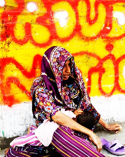 A mother begs at the roadside holding her child in Lahore. Many people in Pakistan are suffering hardship due to price hikes and the poorly performing economy. – Photo by AP