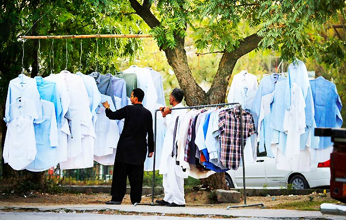 A man browses used shirts on sale, at a makeshift stall along the roadside in Islamabad. – Photo by AP