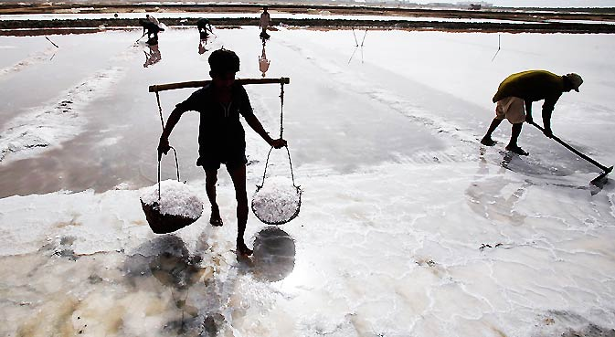 A man carries sea salt harvested from a salt field in Sandspit, in Karachi. Sea salt is produced through solar evaporation of seawaters and is the smallest source of salt in Pakistan. Labourers earn about 600 Pakistan Rupees ($7) a day. The salts are sold commercially by contractors to different industries in Pakistan and overseas.  – Photo by Reuters