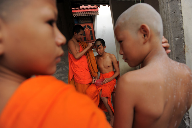 A Buddhist novice monk and aspiring ladyboy Pipop Thanajindawong getting a twice-monthly head shave in a backyard of the Wat Kreung Tai temple.