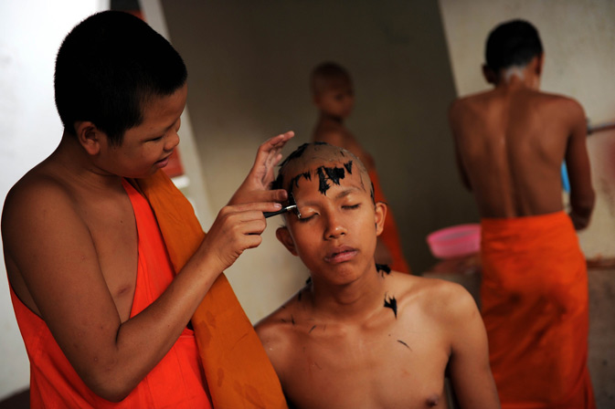 A Buddhist novice monk getting a twice-monthly head shave in a backyard of the Wat Kreung Tai temple.