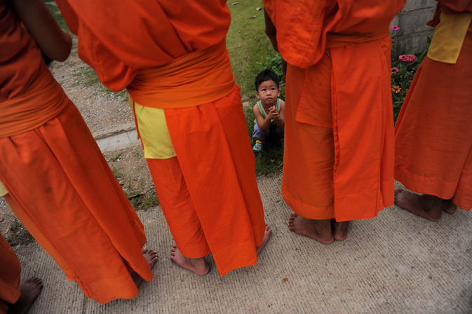 A young boy watching as Buddhist monks from the nearby Wat Kreung Tai temple collect morning alms.