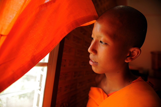 A young Buddhist novice monk and  aspiring ladyboy Pipop Thanajindawong looking outside from his room.