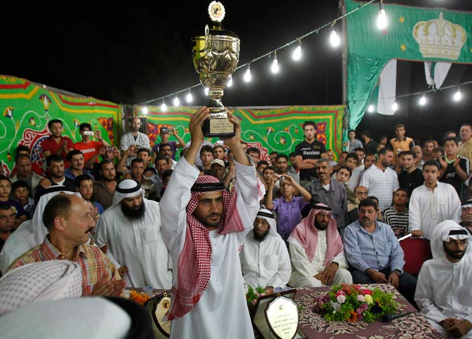 Yeha Abu Jaber lifts a trophy after Wasieef, a Maaz Al Shami (Damascene goat), won the first prize for the ?Most Beautiful Goat? title in the female category at the Mazayen al-Maaz competition.