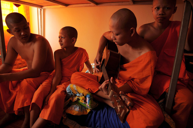 Playing the guitar as others listen in their shared room at the Wat Kreung Tai temple.