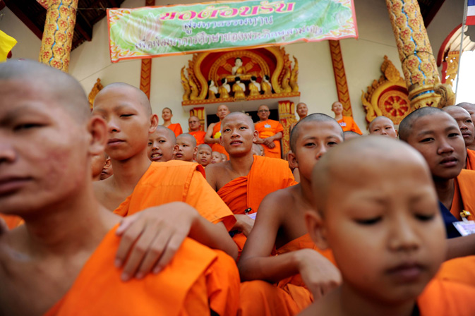 Buddhist novice monks sitting on the steps of the Wat Kreung Tai temple during a small ceremony.