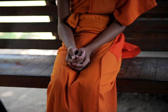An aspiring ladyboy Pipop Thanajindawong's hands as he sits on a bench at the Wat Kreung Tai temple.