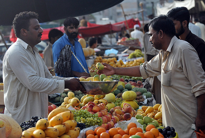A man buys fruit on a roadside stall in Karachi.