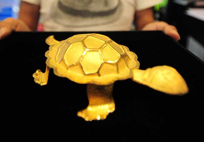 An employee shows a turtle made of gold at a jewellery shop in Seoul on August 19, 2011. The price of gold hit a record high above 1,816 USD an ounce as demand for the safe haven investment rose on resurgent worries about a possible new recession for the global economy.