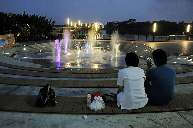 A couple chatting sits in front of a fountain at Singapore's Lower Seletar Reservoir.