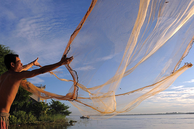 A Cambodian man throws a fishing net in the Mekong river.