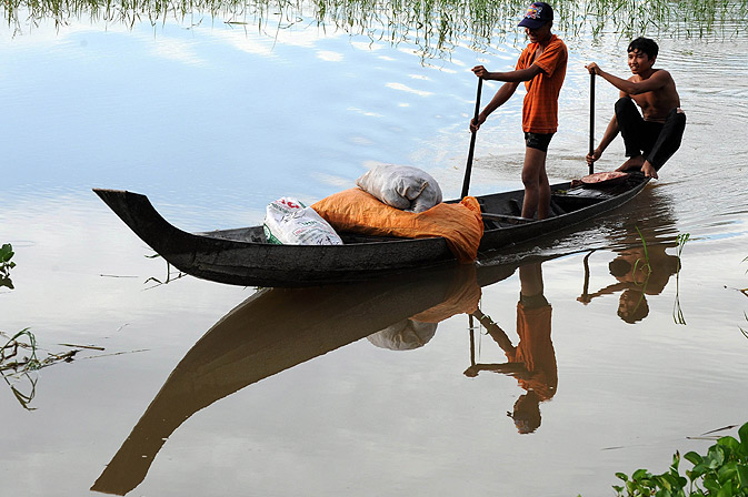Cambodian men row their boat in a lake in Kandal province.