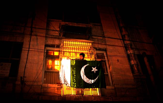 "Mr Jinnah, are you not aware of your surroundings ""This is Planet Pakistan. The spirit of the people over here is what the planet thrives on. Look! This ancient building here comes to life with a glow as that boy fastens a huge flag on his balcony. Come, let me show you more"" — Photo by Nadir Siddiqui/Dawn.com"