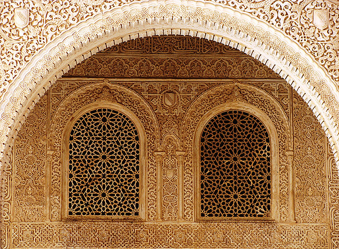 "The central arch and the interior wall of the entrance to the Golden Quarters (Pórtico del Cuarto Dorado). Intricate carvings on the two main walls of this quarter and reflection of light on these walls give the semblance of being surrounded by gold. The interior wall is replete with Nasrid motto while the arch declares ""greatness is God's,"" ""power is God's,"" and ""sovereignty is God's"" in very small carvings. With such elaborate intermingling of forms it is difficult to distinguish the floral and geometrical patter"