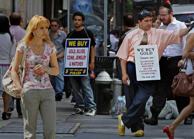 Jewelry traders in the diamond district wear signs advertising to buy gold on Thursday, Aug. 18, 2011 in New York.  Fears from weak global economic reports sent gold up to its latest record high, near US$1,830 an ounce, as traders sought to store their money in the perceived safe haven.