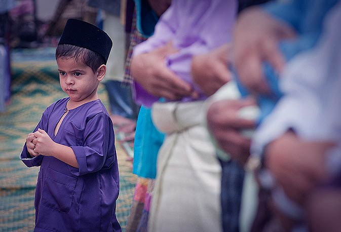 A Malay boy prays with his father on the first day of Eid in Melaka. - AP Photo.