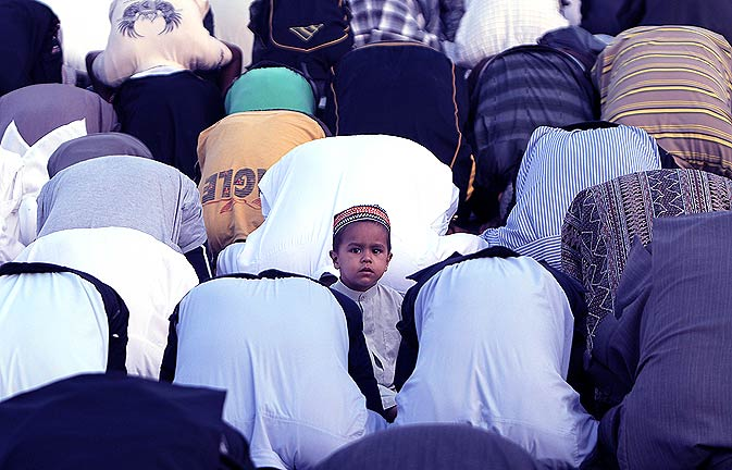 A boy looks up as Muslims pray to celebrate Eid-ul-Fitr at Khan Yunis town in the Gaza strip. - AFP Photo.