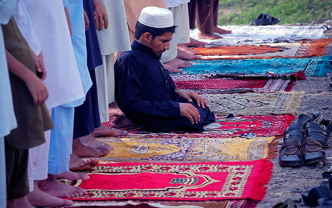 A disabled Afghan refugee offers prayers marking Eid-al-Fitr on Tuesday.