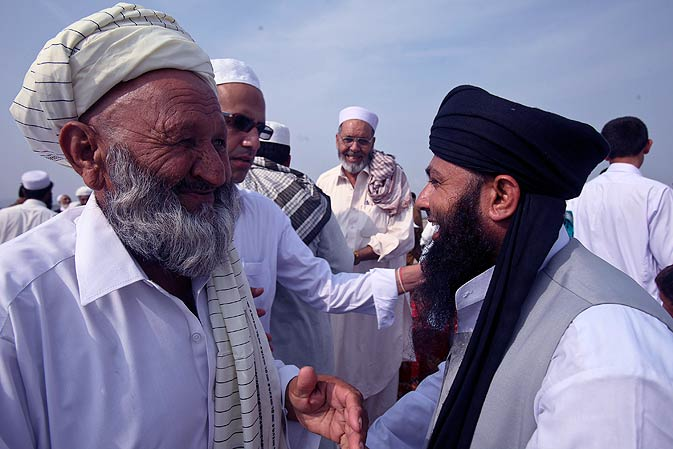 Afghan refugees exchange Eid greetings after offering prayers. - AP Photo.
