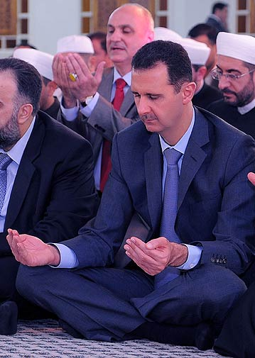 Syrian President Bashar Assad prays the Eid prayer in Damascus on Tuesday. - AP Photo.