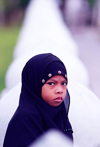 A girl attends prayers outside a mosque in Thailand's southern Pattani province on Tuesday. - Reuters Photo.