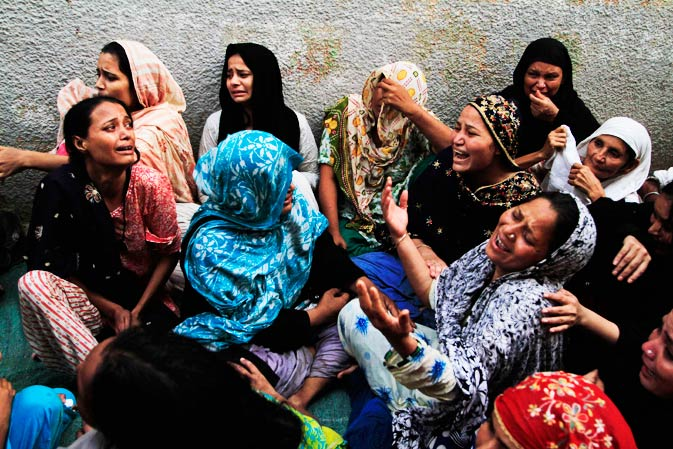 Family members of a target killing victim mourn his death in Karachi, Pakistan on Wednesday, Aug 17, 2011.