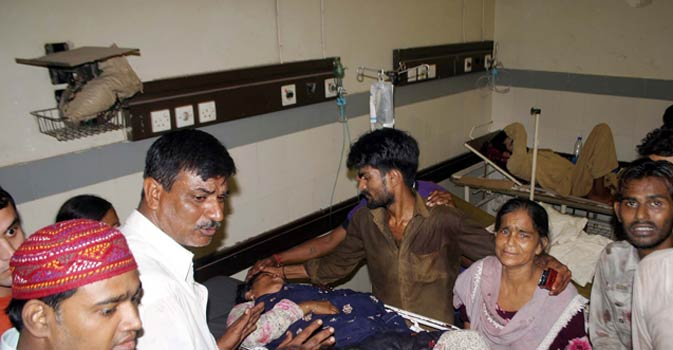 A woman weeps near her injured relative who was wounded during gang warfare in Bheempura area, at Civil Hospital.