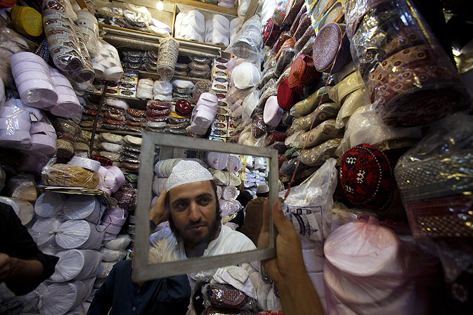 A man buys a traditional cap at a shop in Peshawar.