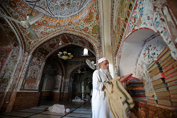 A man selects the Quran for recital in Mohabbat Khan mosque in Peshawar.