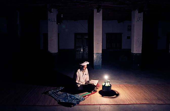 Liaquat Mohammed, 55, an Afghan refugee, reads verses of the Quran, following taraweeh prayers, in a Mosque during the holy month of Ramazan, on the outskirts of Islamabad, Thursday, Aug. 18. - Photo by AP.