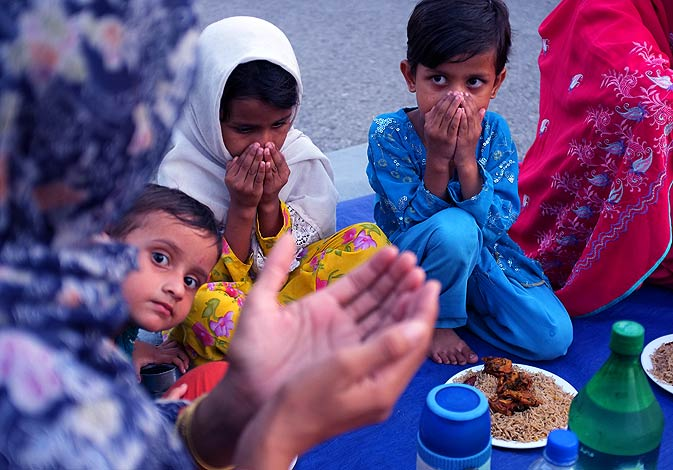 A Pakistani family prays to break their fast in Islamabad Thursday, Aug. 18. - Photo by AP.