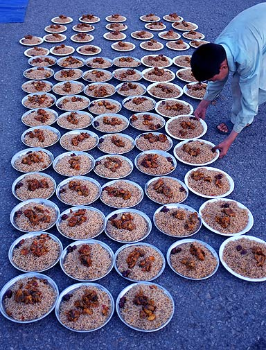 A Pakistani boy collects food to serve people gathered to break their fast in Islamabad on Thursday. - Photo by AP.