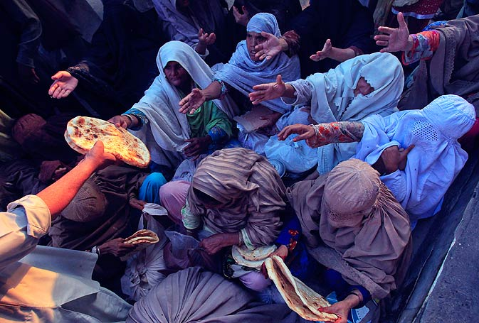 Women reach out to receive bread that were donated for Iftar in Peshawar on Wednesday. - Photo by Reuters.