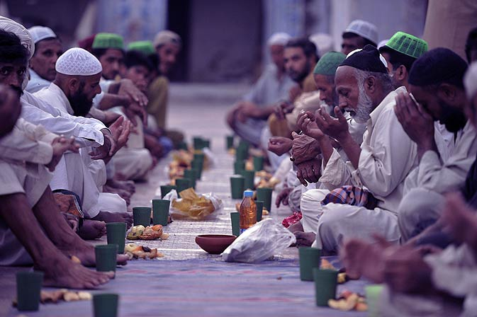 Pakistani Muslims pray prior to breaking their fast on Wednesday. - Photo by AFP.