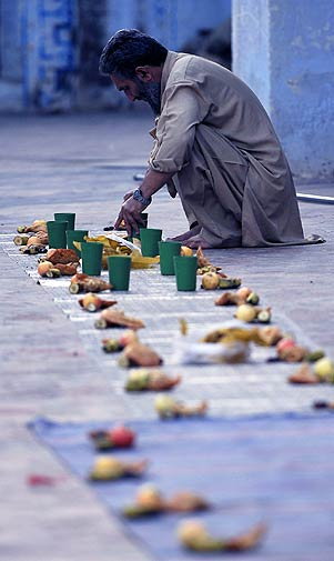 A Pakistani man arranges food for observers of the holy fasting month of Ramazan at sunset in a mosque in Rawalpindi on Wednesday. - Photo by AFP.