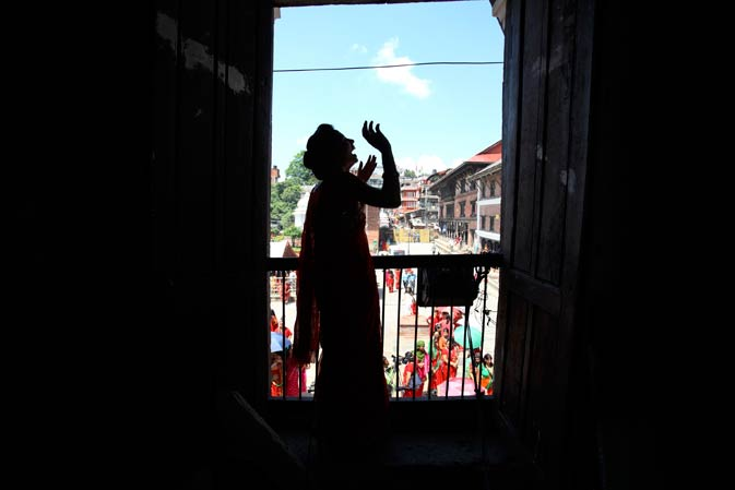 A woman sings and dances as she watches her friends from a window during the Teej festival at Pashupatinath Temple in Kathmandu, August 31, 2011.