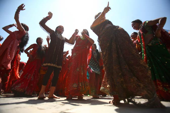 Women sing and dance at Pashupatinath Temple.