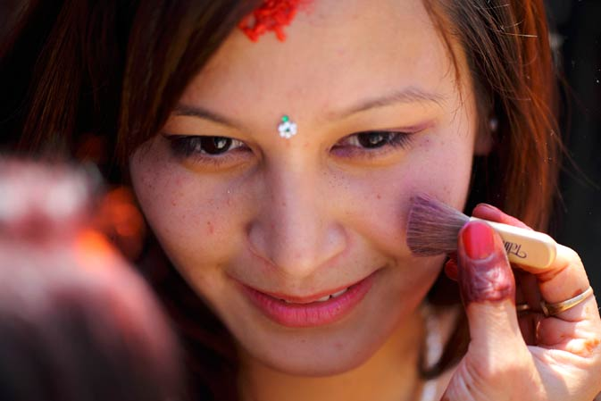 A woman is seen as her friend applies make up on her face during the festival.