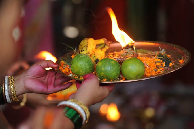 An offering plate is seen as a woman offers prayers to Lord Shiva.