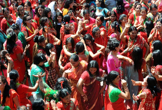 Nepalese Hindu women dressed in red, dance after paying homage to Shiva as they celebrate the festival in Kathmandu.