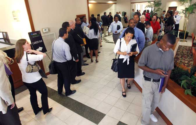 In this Aug. 15, 2011 photo, a line of job seekers, waiting to see recruiters, twists through a hotel lobby during a career fair in Plano, Texas.