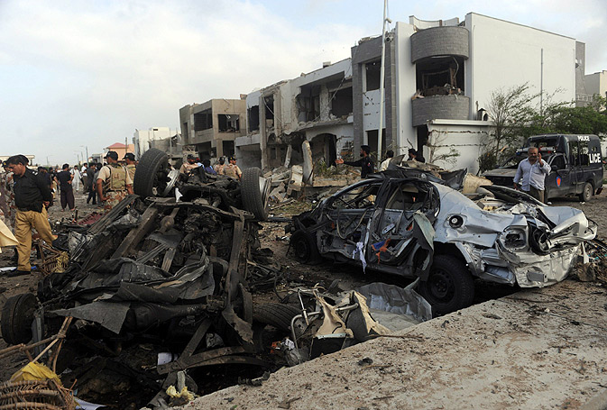 Security personnel gather at the car bomb blast site.