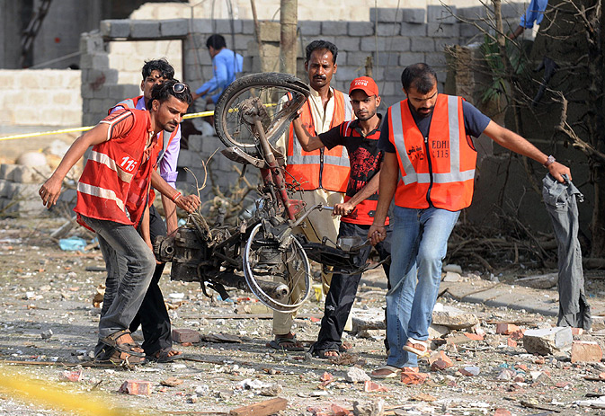 Edhi volunteers carry the carcass of a motorcycle.