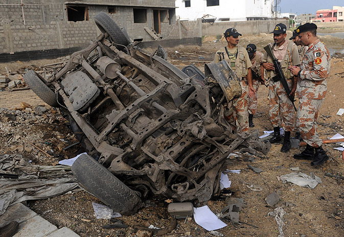 Paramilitary soldiers inspect a destroyed vehicle.