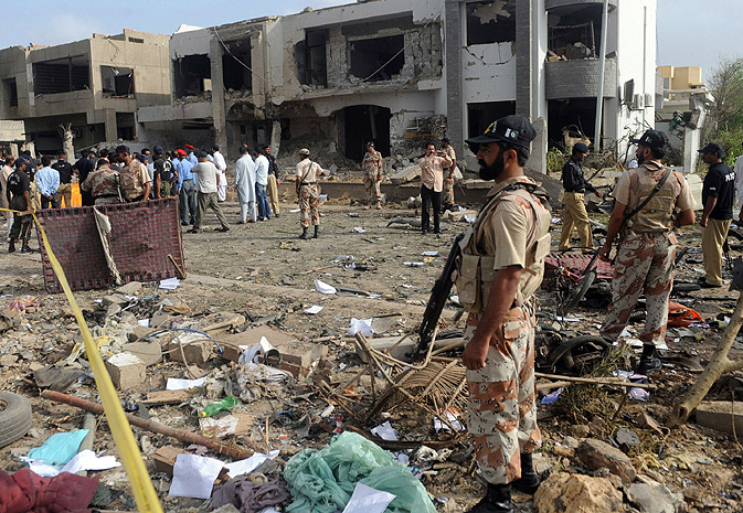 Security personnel gather at the site of the bomb blast.